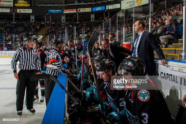Linesman Tim Plamondon and referee Jeff Ingram stand on the ice at the Kelowna Rockets' bench and speak to head coach Jason Smith and assistant coach...