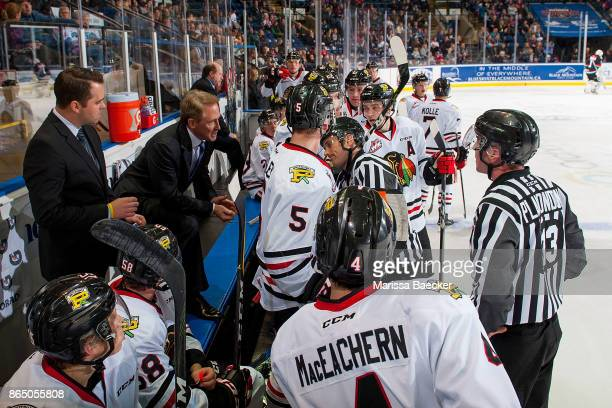 Linesman Tim Plamondon and referee Jeff Ingram stand on the ice at the Portland Winterhawks' bench and speak to head coach Mike Johnston and...