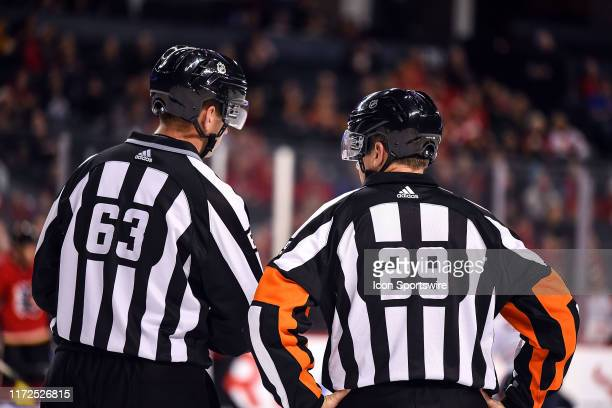 Linesman Trent Knorr and Referee Ian Walsh talk between plays during the third period of an NHL game where the Calgary Flames hosted the Edmonton...