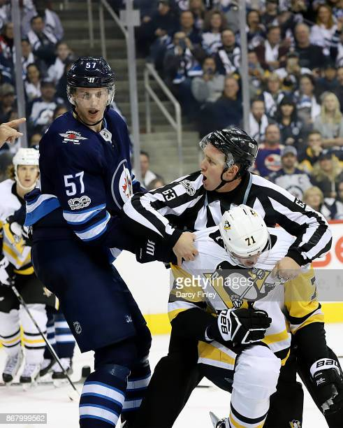 Linesman Trent Knorr separates Tyler Myers of the Winnipeg Jets and Evgeni Malkin of the Pittsburgh Penguins following a third period scrum at the...