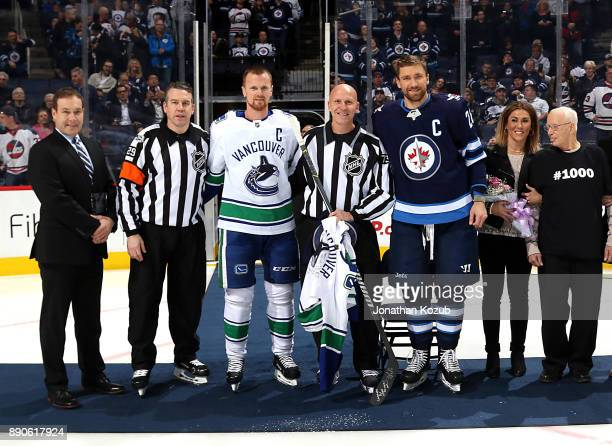 Linesman Vaughan Rody poses with NHL Senior Vice President and Director of Officiating Stephen Walkom referee Ian Walsh Henrik Sedin of the Vancouver...