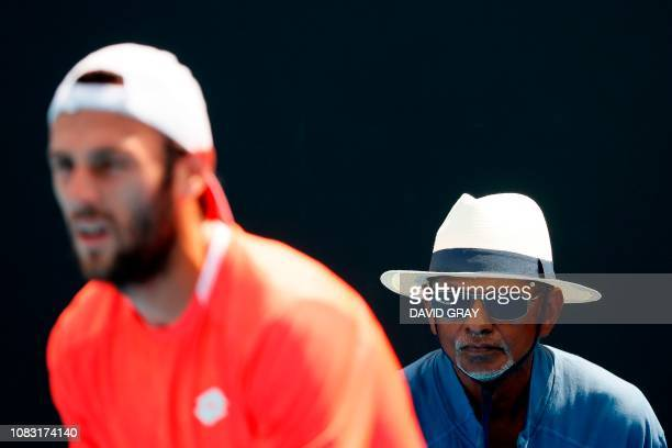 A linesman watches as Georgia's Nikoloz Basilashvili plays against Italy's Stefano Travaglia during their men's singles match on day three of the...