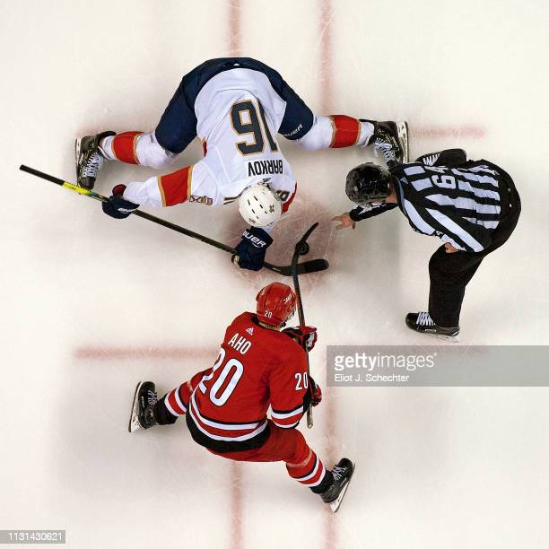 Linesmen Brandon Gawryletz drops the puck for a face off between Aleksander Barkov of the Florida Panthers and Sebastian Aho of the Carolina...