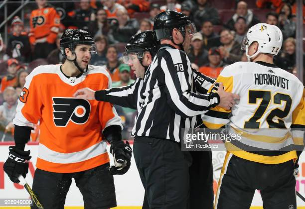 Linesmen Brian Mach and Michel Cormier separate Brandon Manning of the Philadelphia Flyers and Patric Hornqvist of the Pittsburgh Penguins during a...