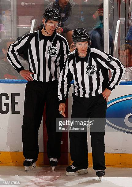 Linesmen Brian Murphy and Steve Barton chat on the ice during a break in the action between the Florida Panthers and the Tampa Bay Lightning at the...