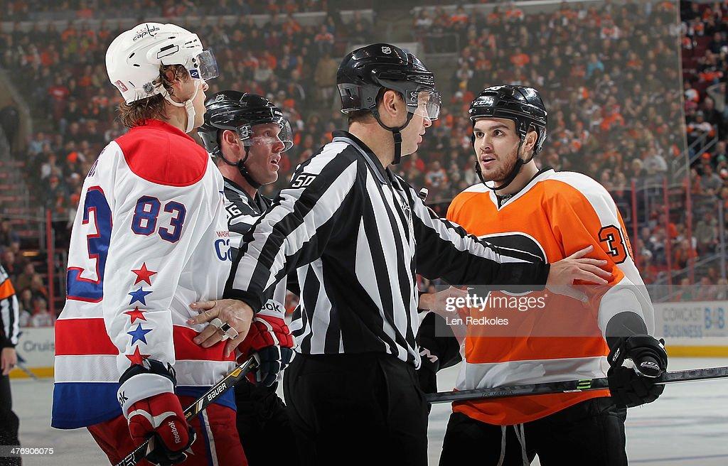 Linesmen David Brisebois #96 and Scott Cherrey #50 separate Zac Rinaldo #36 of the Philadelphia Flyers and Jay Beagle #83 of the Washington Capitals on March 5, 2014 at the Wells Fargo Center in Philadelphia, Pennsylvania. The Flyers went on to defeat the Capitals 6-4.