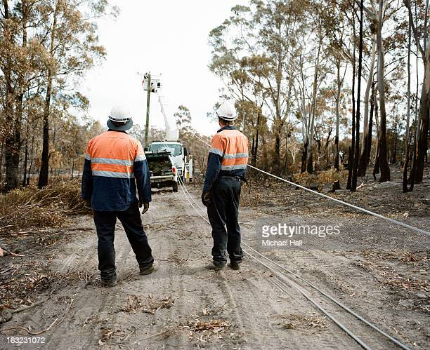 linesmen erecting power lines after fire - australia fire stock pictures, royalty-free photos & images