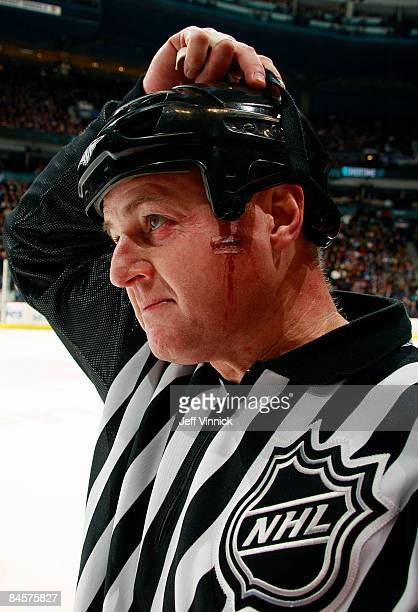 Linesmen Lonnie Cameron sports a cut on his cheek after getting hit by a puck during the game between the Vancouver Canucks and the Minnesota Wild at...