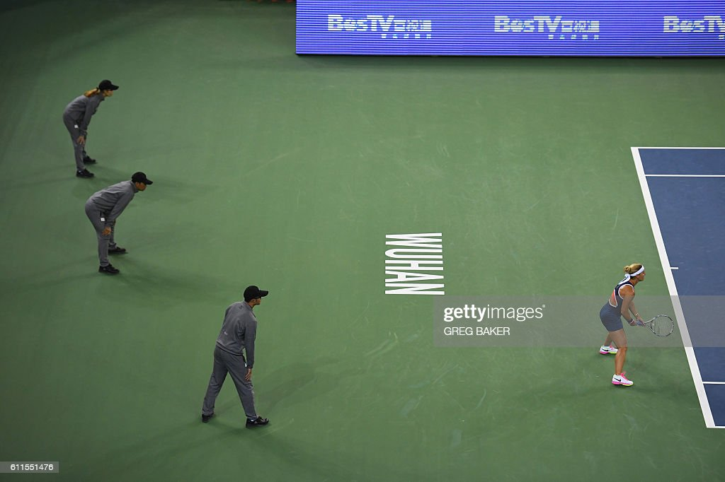 TOPSHOT - Linesmen look on as Dominika Cibulkova (R) of Slovakia prepares to receive serve during her semi-final match against Svetlana Kuznetsova of Russia at the WTA Wuhan Open tennis tournament in Wuhan, in China's central Hubei province on September 30, 2016. / AFP / GREG