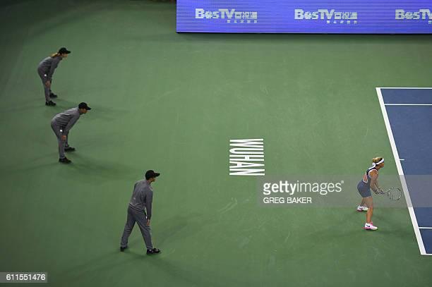 TOPSHOT Linesmen look on as Dominika Cibulkova of Slovakia prepares to receive serve during her semifinal match against Svetlana Kuznetsova of Russia...