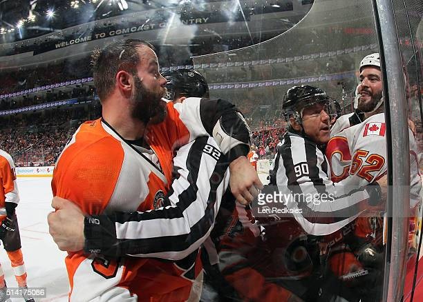Linesmen Mark Shewchyk and Andy McElman restrain Radko Gudas of the Philadelphia Flyers and Brandon Bollig of the Calgary Flames during a scrum on...