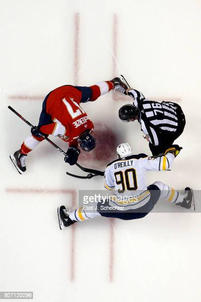 Linesmen Michel Cormier drops the puck for a face off between Derek MacKenzie of the Florida Panthers and Ryan O'Reilly of the Buffalo Sabres at the...
