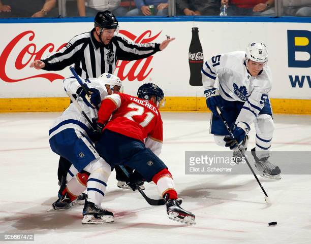 Linesmen Michel Cormier signals while Jake Gardiner of the Toronto Maple Leafs skates with the puck with teammate Tomas Plekanec shoving Vincent...