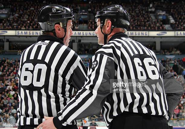 Linesmen Pat Dapuzzo and Darren Gibbs share a few words during a break in the NHL game between the Los Angeles Kings and the Vancouver Canucks at...