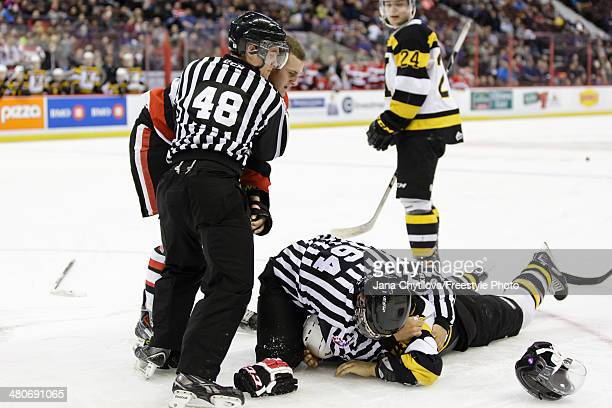 Linesmen Pat Smith and Dave Borden separate Ryan Van Stralen of the Ottawa 67's and Loren Ulett of the Kingston Frontenacs following a fight during...