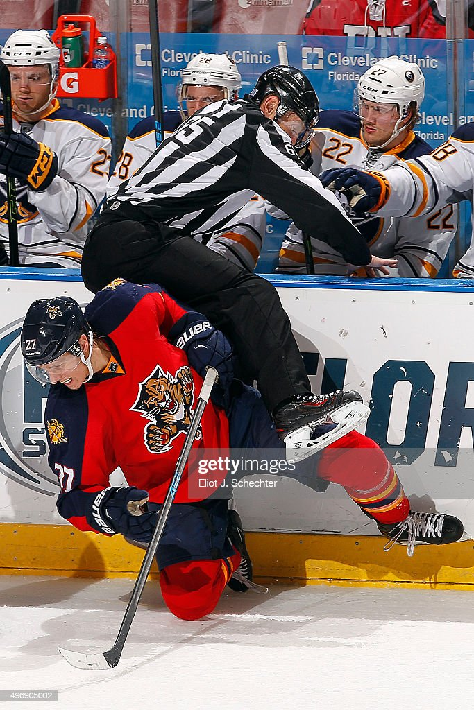 NHL Linesmen Pierre Racicot #65 tries to get out of the way of Nick Bjugstad #27 of the Florida Panthers in front of the Buffalo Sabres bench at the BB&T Center on November 12, 2015 in Sunrise, Florida.