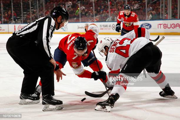Linesmen Scott Cherry drops the puck for a face off between Brett Seney of the New Jersey Devils and Colton Sceviour of the Florida Panthers at the...