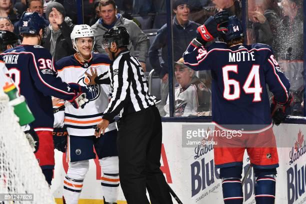Linesmen Shandor Alphonson breaks up a scuffle between Matt Benning of the Edmonton Oilers and Tyler Motte of the Columbus Blue Jackets during the...