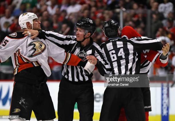Linesmen Steve Barton and Brandon Gawryletz get between Ryan Getzlaf of the Anaheim Ducks and Richard Panik of the Chicago Blackhawks during a fight...