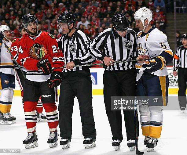 Linesmen Steve Barton and Scott Cherrey untangle the sticks of Phillip Danault of the Chicago Blackhawks and Barret Jackman of the Nashville...