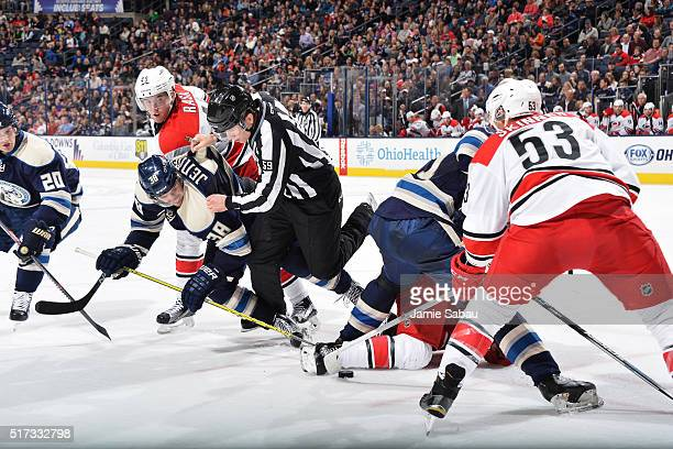 Linesmen Steve Barton attempts to skate away from a faceoff as players from both teams battle for the puck during a game between the Columbus Blue...