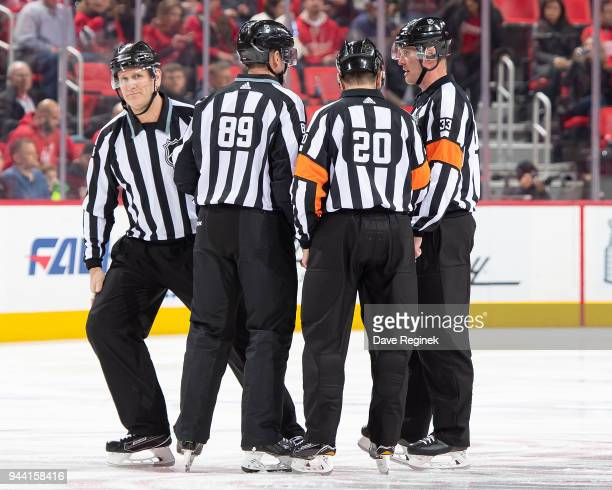 Linesmen Steve Miller and Greg Devorski along with Referee's Tim Peel and Kevin Pollock gather at center ice before the start of an NHL game between...