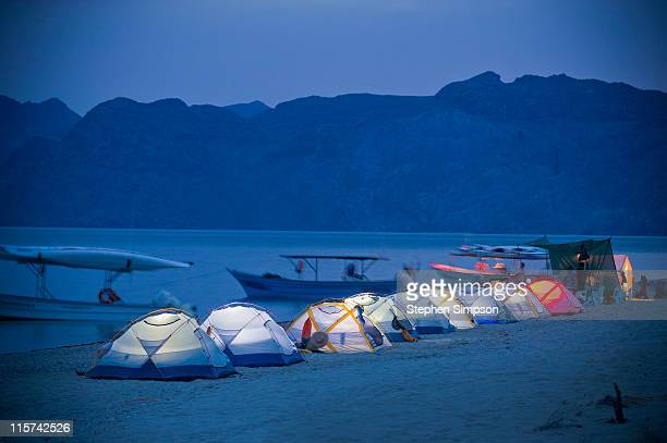 line-up of glowing tents on the beach