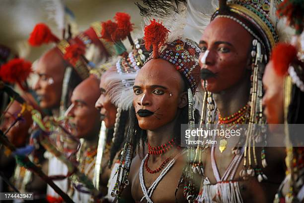 Lineup of men with red faces and tribal beads