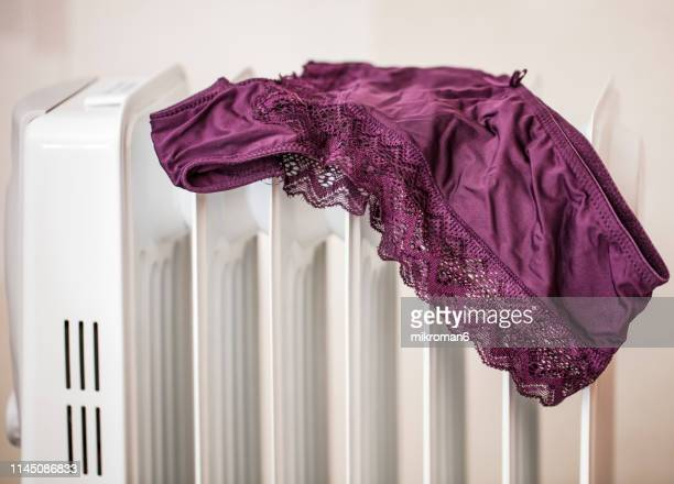 lingerie drying on electric heater convector at home. - knickers photos stock pictures, royalty-free photos & images