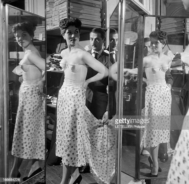 Lingerie In 1956 En 1956 dans l'atelier d'un tailleur devant un triple miroir une jeune femme et son reflet en sous v¿¿tement bustier blanc un coupon...