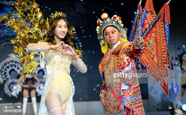 A lingerie model poses with a Beijing Opera performer at a mall on July 19 2018 in Jinan Shandong Province of China