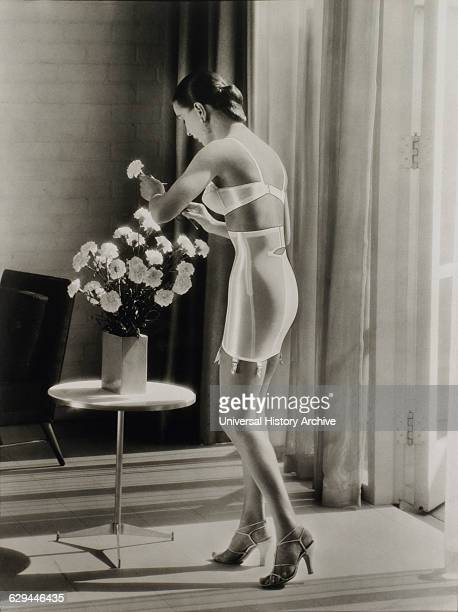 Lingerie Model Wearing Bra and Corset Putting Flowers in Vase circa 1950
