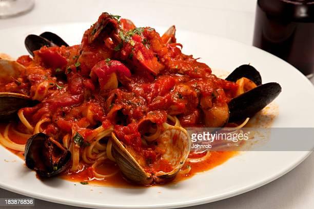 linguini with seafood, calamari, clams, mussels, shrimp, scungilli, marinara sauce - marinara stock photos and pictures