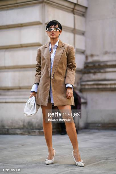 Linh Dang Kang Nguyen wears sunglasses, a brown oversized blazer jacket, a shirt, a white puff bag, white pointy shoes, during London Fashion Week...