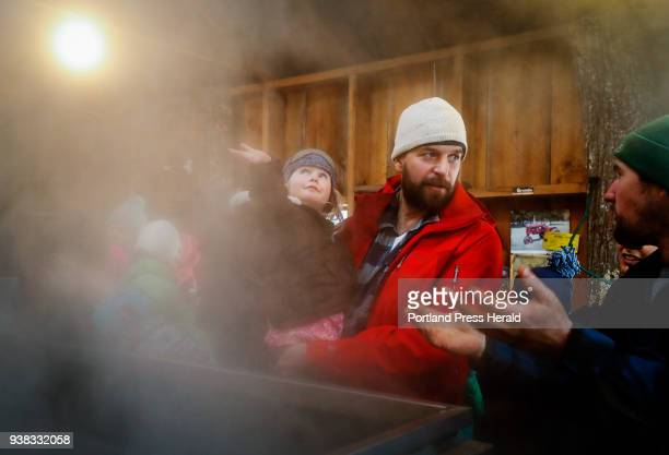 Linnea Miller left runs her hand through the steam from the evaporator as her father Brent center speaks with Adam Parsons right during a tour of the...