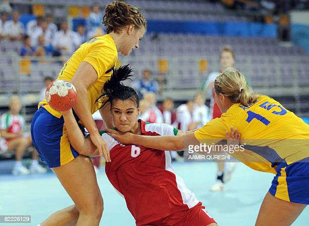 Linnea Torstenson and teammate Johanna Ahlm of Sweden try to stop Hungary's Orsolya Verten during their 2008 Olympics Games handball match on August...