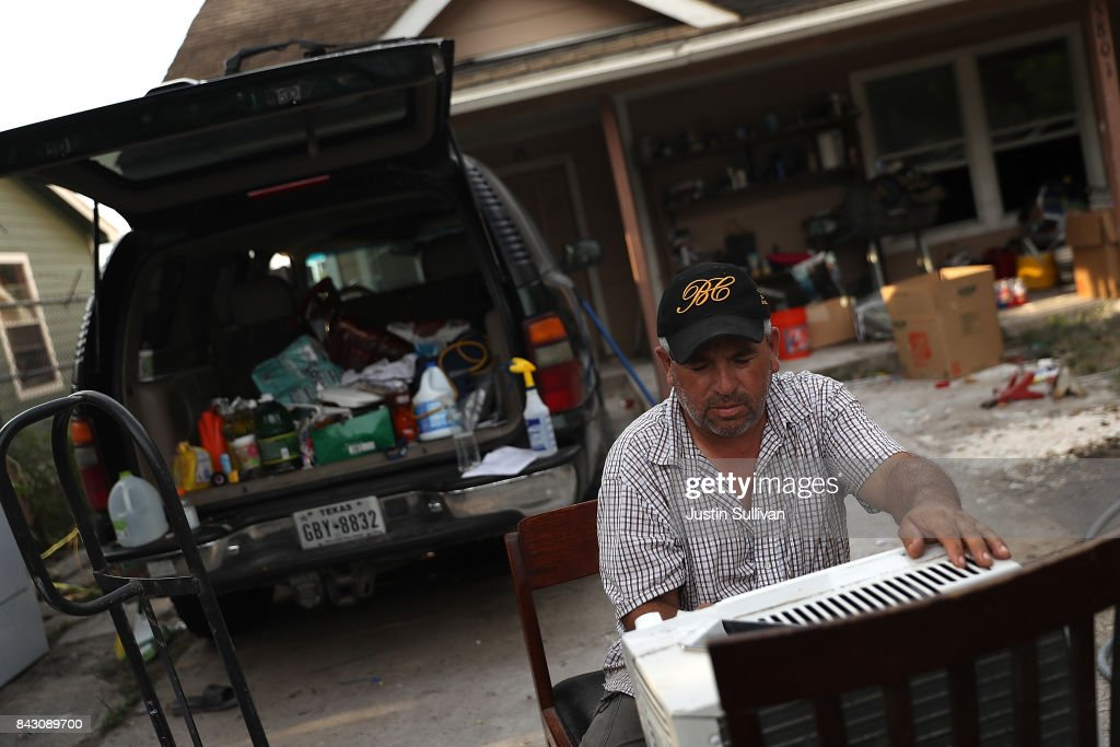 Lino Saldana tries to repair a broken air conditioner in front of his flood damaged home on September 5, 2017 in Houston, Texas. Over a week after Hurricane Harvey hit Southern Texas, residents are beginning the long process of recovering from the storm.