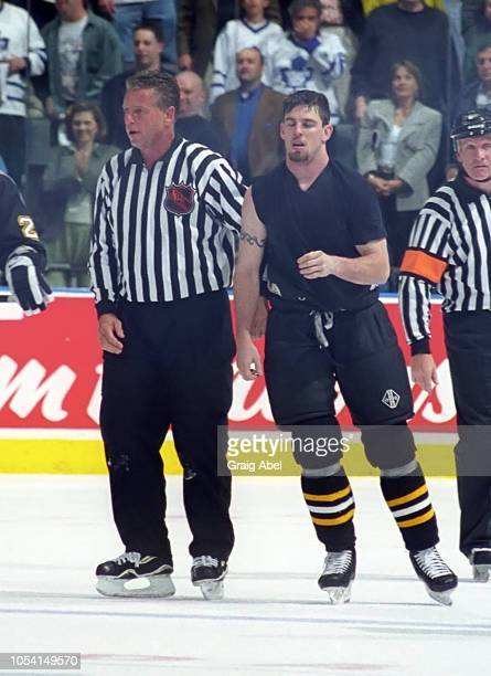 Linseman Gord Broseker escorts Matthew Barnaby of the Pittsburgh Penguins to the penalty box against the Toronto Maple Leafs during the 1999 Quarter...