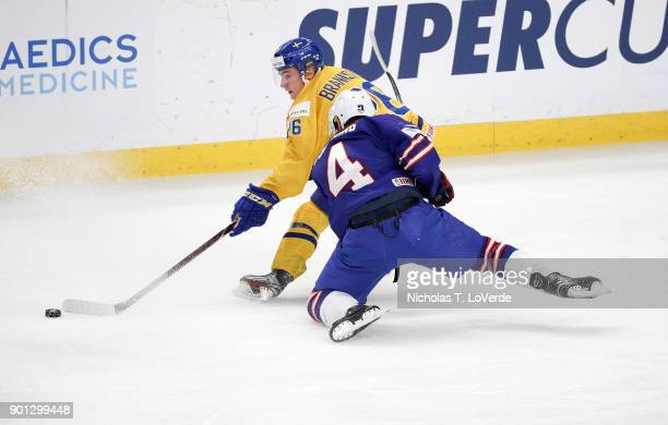 Linus Lindström of Sweden battles with Ryan Poehling of United States for a loose puck during the second period of play in the IIHF World Junior...