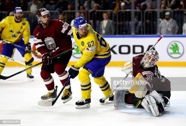 Linus Omark of Sweden fails to score over Elvis Merzlikins goaltender of Latvia during the 2017 IIHF Ice Hockey World Championship game between...