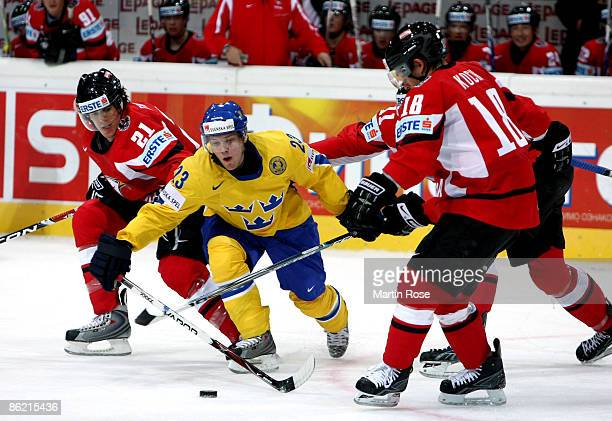 Linus Omark of Sweden fights for the puck with Matthias Trattnig and Thomas Koch of Austria during the IIHF World Ice Hockey Championship preliminary...
