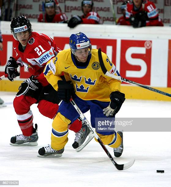 Linus Omark of Sweden fights for the puck with Matthias Trattnig of Austria during the IIHF World Ice Hockey Championship preliminary round, group C...