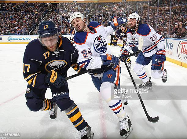 Linus Omark of the Buffalo Sabres battles for position along the boards as Ryan Smith of the Edmonton Oilers takes hold of his stick during the third...