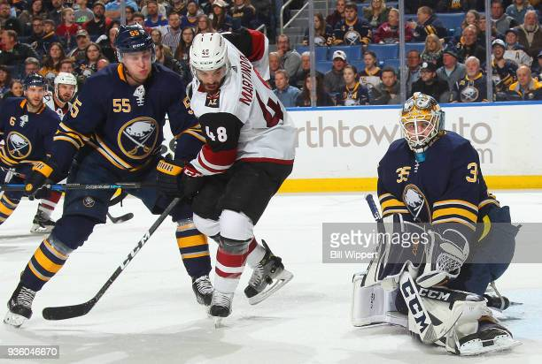 Linus Ullmark and Rasmus Ristolainen of the Buffalo Sabres defend the net against Jordan Martinook of the Arizona Coyotes during an NHL game on March...