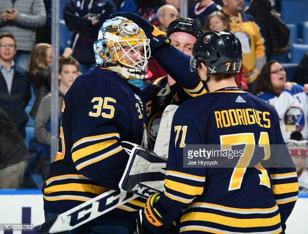 Linus Ullmark of the Buffalo Sabres celebrates their 31 victory against the Columbus Blue Jackets with Jack Eichel and Evan Rodrigues after an NHL...