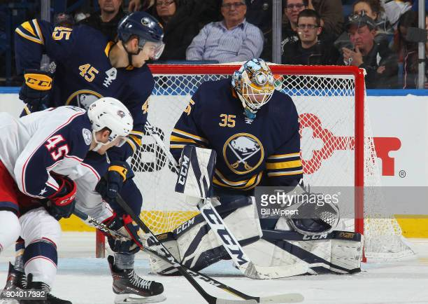 Linus Ullmark of the Buffalo Sabres makes a save as Brendan Guhle defends against the Columbus Blue Jackets during an NHL game on January 11 2018 at...