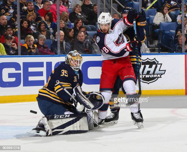 Linus Ullmark of the Buffalo Sabres makes a save as Oliver Bjorkstrand of the Columbus Blue Jackets looks for a rebound while defended by Jake McCabe...