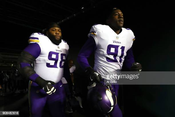 Linval Joseph and Stephen Weatherly of the Minnesota Vikings walk out on the field for warm ups prior to the NFC Championship game against the...