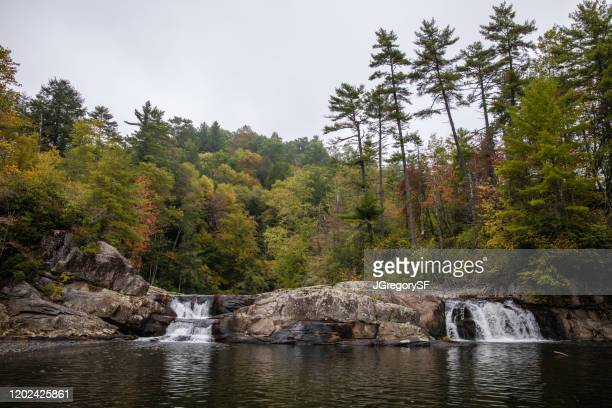 linville falls in autumn - waterfall with colorful trees above - day time - backgrounds - blue ridge parkway stock pictures, royalty-free photos & images