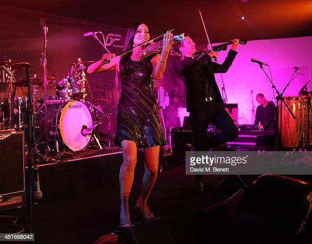 Linzi Stoppard and Ben Lee perform on stage at The Grand Prix Ball at the Royal Artillery Gardens on July 3 2014 in London England